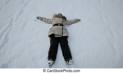 Girl playing in the snow angel