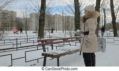 Little girl playing in snowballs