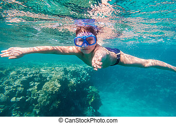Boy in swimming mask dive in Red sea near coral reef,...