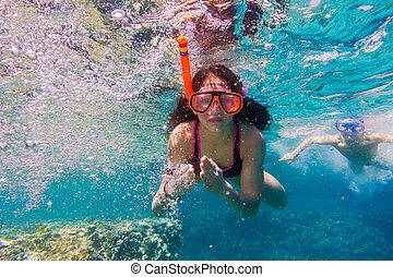 Girl and boy in swimming mask dive in Red sea near coral...