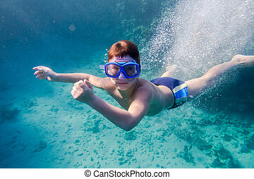 Boy in swimming mask deep dive in Red sea near coral reef,...