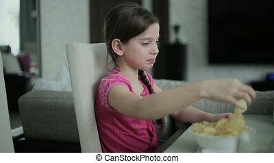 Little girl eating potato chips.