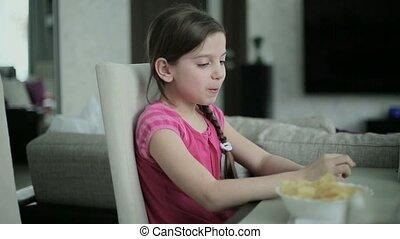 Little girl eating potato chips