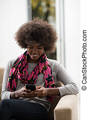 black woman sitting on sofa and using mobile phone - young...