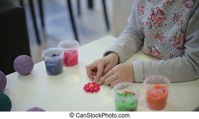 Girl sculpts clay figure flower