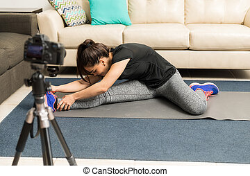 Fitness blogger giving advice on stretching - Young woman in...