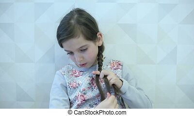 Little girl combs her hair