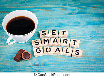 set smart goals. Coffee mug and wooden letters on wooden...