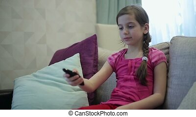 Girl manages remote control tv.