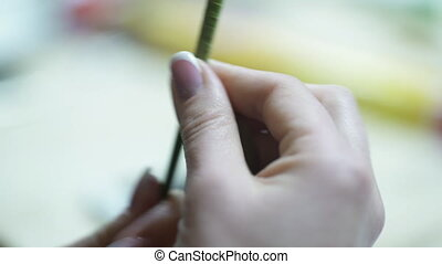 Female hands florist twisted green stem for an artificial bouquet.