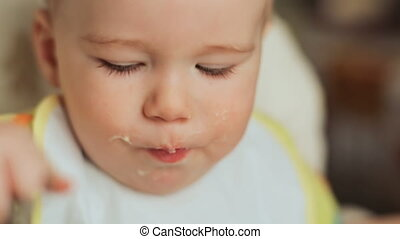 Mother feeds her capricious child. Gives him porridge and gives him juice. Face close-up.