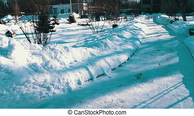 Snow covered walkway of park. - Winter snow-covered path in...
