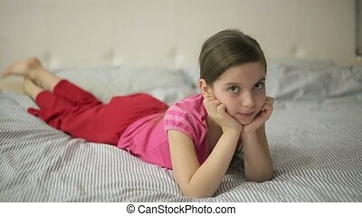 Girl lying on the bed moves feet