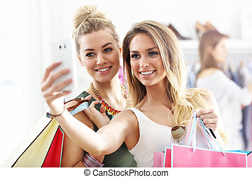 Happy friends shopping in store with smartphone - Picture...