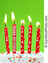 Colorful birthday candles on green background