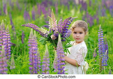 Little girl at the green field in sunset time, with bouquet