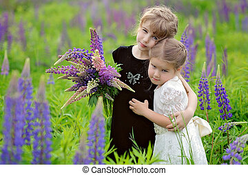 Two little girls at the green field in sunset time, with bouquet