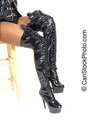 Woman sitting in long black boots.