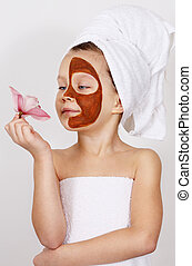 mask on her face - Little Girl with a clay mask on her face