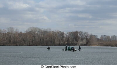 Winter fishing in the middle of a frozen lake. - Group of...