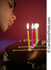 Little girl blowing birthday chocolate cake candles