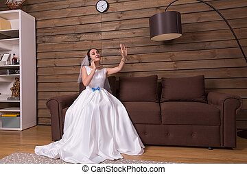 Bride talking by phone, looking at wedding ring - Portrait...
