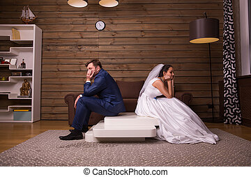 Unhappy family couple sitting on the table