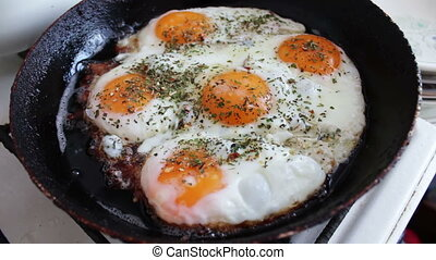Morning fried eggs is roasted in a pan on the home kitchen -...