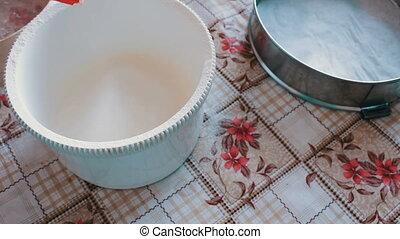 Woman pours flour into a bowl