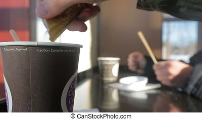 Hand pours sugar into a disposable cup after stir. Action...
