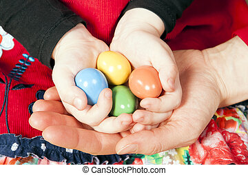 Little girl holding Easter eggs in her and mother's hands.