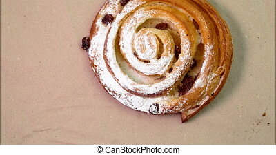 Buns with raisins rotates on a paper background top view....