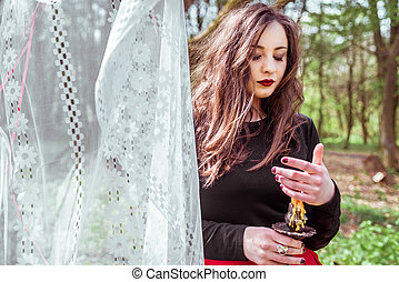 witch in the woods with a candle - mysterious woman witch in...