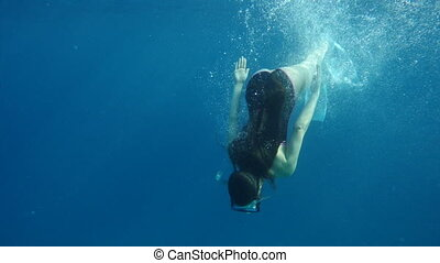 Girl dive in the sea with underwater mask, slow motion