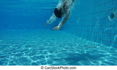 Boy in swimming pool swim underwater, slow motion