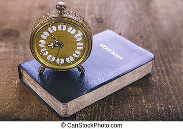 Holy Bible and old alarm clock on wood table - Holy Bible...