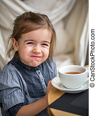 little girl drinking tea in a cafe ,the concept of Breakfast...
