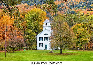 Historic church in Royalton, Vermont with foliage background