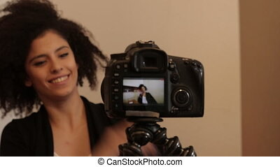 Smiling young female shooting self video - Young female...