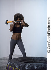 black woman workout with hammer and tractor tire