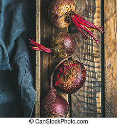 Raw organic purple beetroots in wooden box, square crop -...