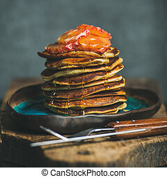 Homemade pancakes with honey and bloody orange slices,...