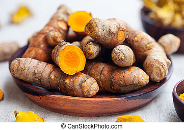 Fresh and dried turmeric roots in a wooden bowl. Grey...