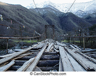 Old wooden bridge hanging over gorge and mountain stream....