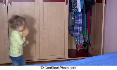 Adorable child kid hide best friend teddy bear into closet and close door