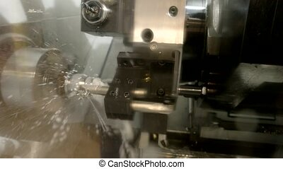 Metal lathe in action. Machine and water splashing.