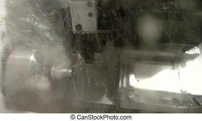 Action of lathe machine. Splashes of liquid. Water as a...