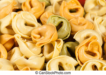 Background of colored tortellini, ring-shaped pasta, close...