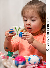 little girl draws paints Easter eggs, the concept of the...