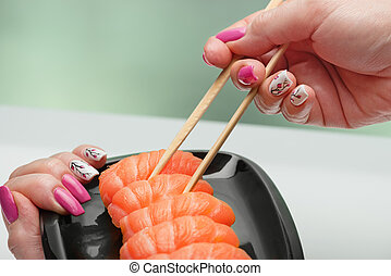 The female hand with magnificent manicure takes sushi with a...
